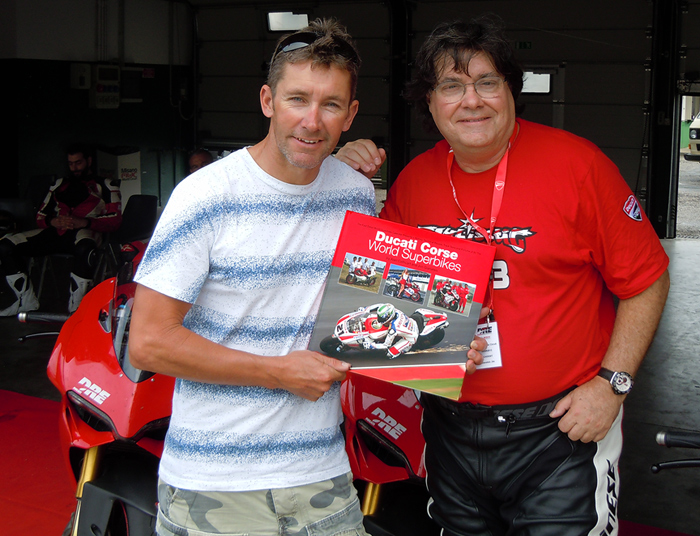 Troy bayliss receives Cucati Corse World Superbikes book from Jim Gianatsis